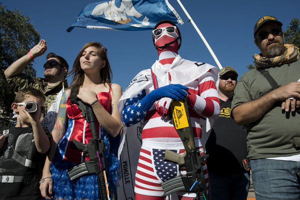 "A couple from Austin, dressed as superheros at the ""Come and Take it Rally"" in San Antonio, Texas. Hundreds of gun rights demonstrators came with loaded firearms to stage a rally at the Alamo -- the site where in 1836 Texas defenders were killed by the Mexican Army -- to prove their right to openly carry firearms including military style AR-15s.  The rally was the largest of smaller gatehrings that have been happening across the USA, where gun owners are asserting their right to openly carry weapons on the street and in commercial establishments.   Participants came from across Texas and included ranchers, young Austin professionals, and veterans.   Some were affiliated with the Tea Party movement and compared their defense of gun rigts to greater issues of freedom that they say are being eroded by the Obama Administration -- specifically - the Obama Health Law or Obama Care."